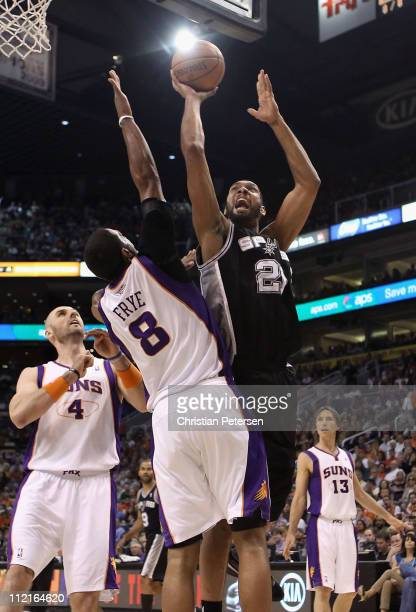 Tim Duncan of the San Antonio Spurs puts up a shot over Channing Frye of the Phoenix Suns during the NBA game at US Airways Center on April 13 2011...