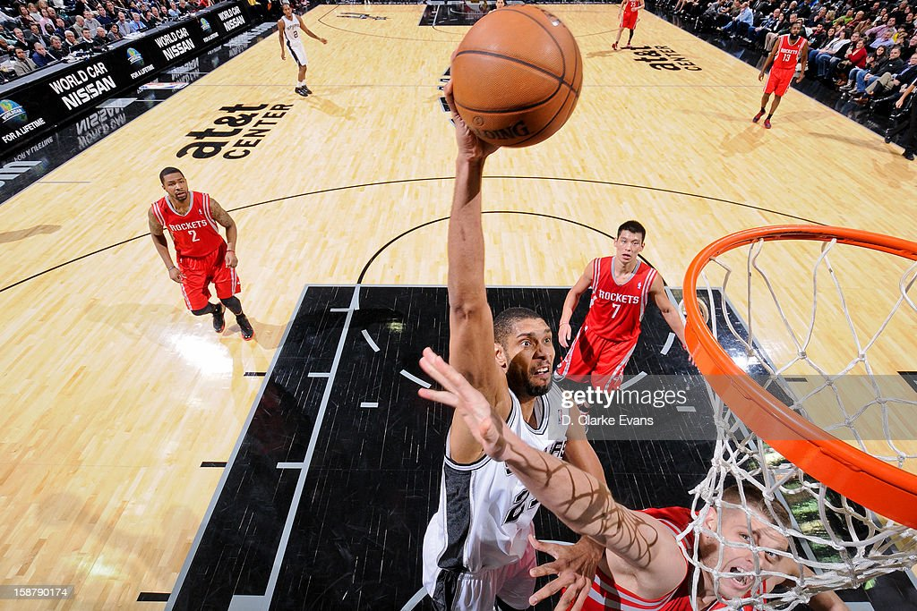 Tim Duncan #21 of the San Antonio Spurs rises for a dunk against Cole Aldrich #31 of the Houston Rockets on December 28, 2012 at the AT&T Center in San Antonio, Texas.