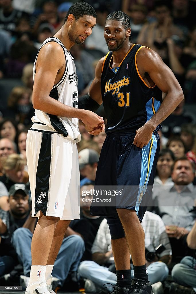 Tim Duncan #21 of the San Antonio Spurs shares a laugh with Nene #31 of the Denver Nuggets in Game One of the Western Conference Quarterfinals during the 2007 NBA Playoffs at AT&T Center on April 22, 2007 in San Antonio, Texas. The Nuggets won 95-89.