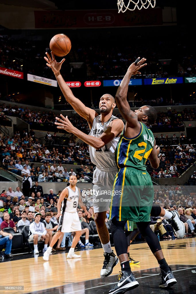 Tim Duncan #21 of the San Antonio Spurs shoots a layup against Paul Millsap #24 of the Utah Jazz on March 22, 2013 at the AT&T Center in San Antonio, Texas.
