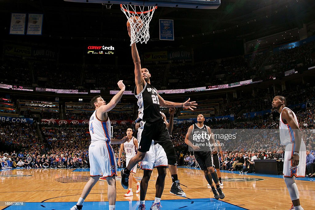 Tim Duncan #21 of the San Antonio Spurs shoots a layup ahead of Nick Collison #4 of the Oklahoma City Thunder on April 4, 2013 at the Chesapeake Energy Arena in Oklahoma City, Oklahoma.