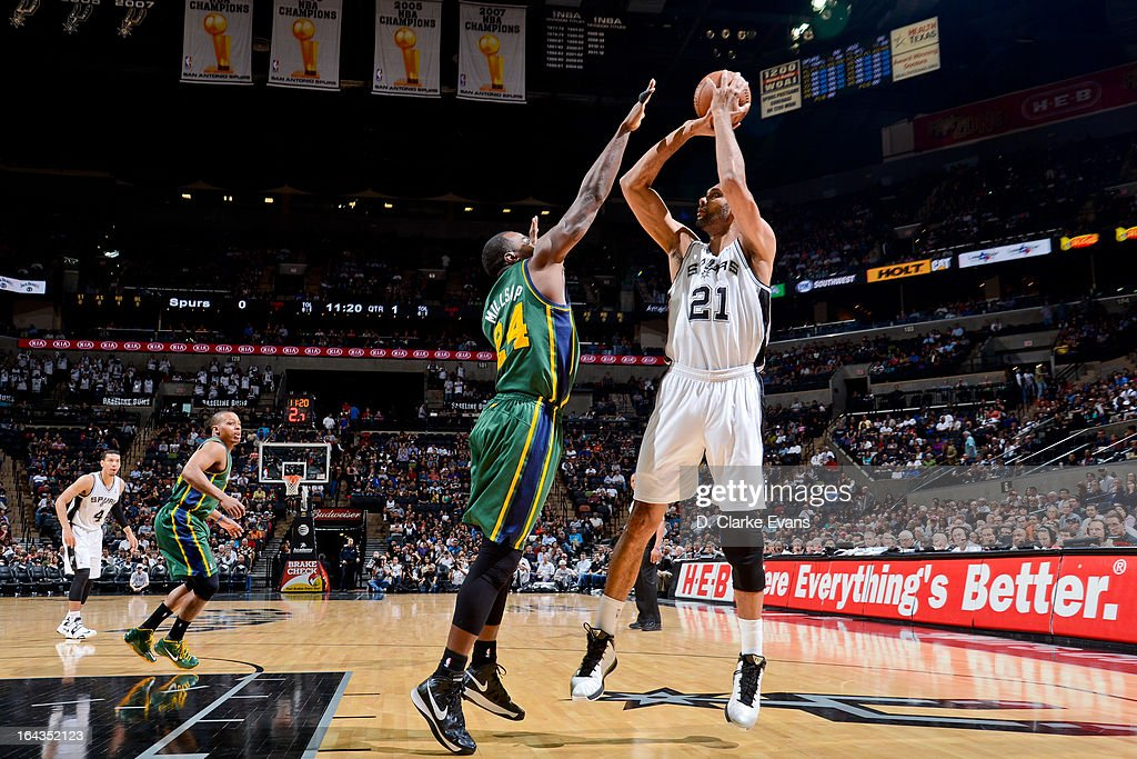 Tim Duncan #21 of the San Antonio Spurs shoots against Paul Millsap #24 of the Utah Jazz on March 22, 2013 at the AT&T Center in San Antonio, Texas.