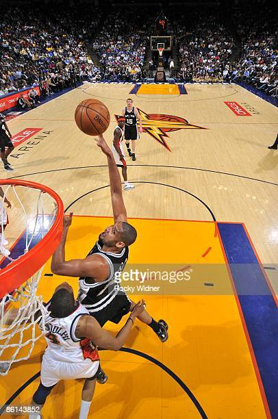Tim Duncan of the San Antonio Spurs shoots over Anthony Randolph of the Golden State Warriors during the game at Oracle Arena on April 13 2009 in...