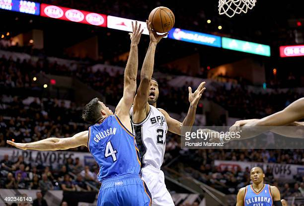 Tim Duncan of the San Antonio Spurs shoots over Nick Collison of the Oklahoma City Thunder in the first quarter in Game One of the Western Conference...