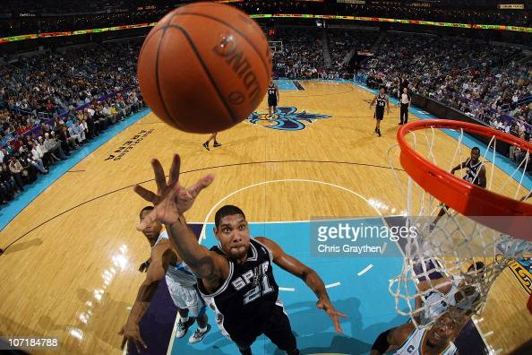 Tim Duncan of the San Antonio Spurs shoots the ball over David West of the New Orleans Hornets at the New Orleans Arena on November 28 2010 in New...