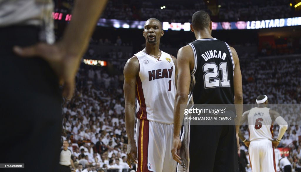 Tim Duncan (R) of the San Antonio Spurs stands on court with Chris Bosh (L) of the Miami Heat during Game 7 of the NBA Finals at the American Airlines Arena June 20, 2013 in Miami, Florida. AFP PHOTO / Brendan SMIALOWSKI