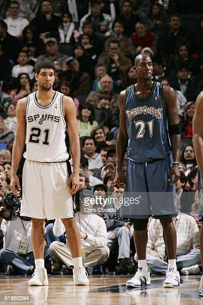 Tim Duncan of the San Antonio Spurs stands on the court next to Kevin Garnett of the Minnesota Timberwolves during the game on December 23 2004 at...