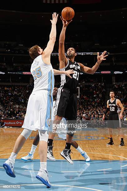 Tim Duncan of the San Antonio Spurs takes a shot over Timofey Mozgov of the Denver Nuggets at Pepsi Center on December 14 2014 in Denver Colorado...