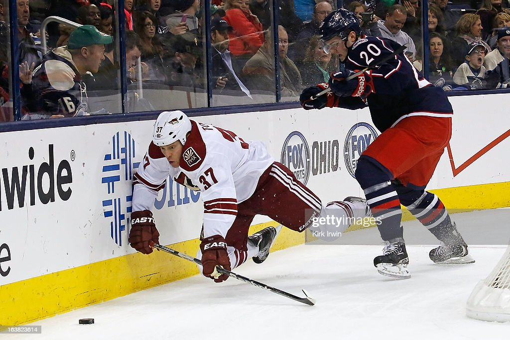 Tim Erixon #20 of the Columbus Blue Jackets checks Raffi Torres #37 of the Phoenix Coyotes while chasing after a loose puck during the first period on March 16, 2013 at Nationwide Arena in Columbus, Ohio.