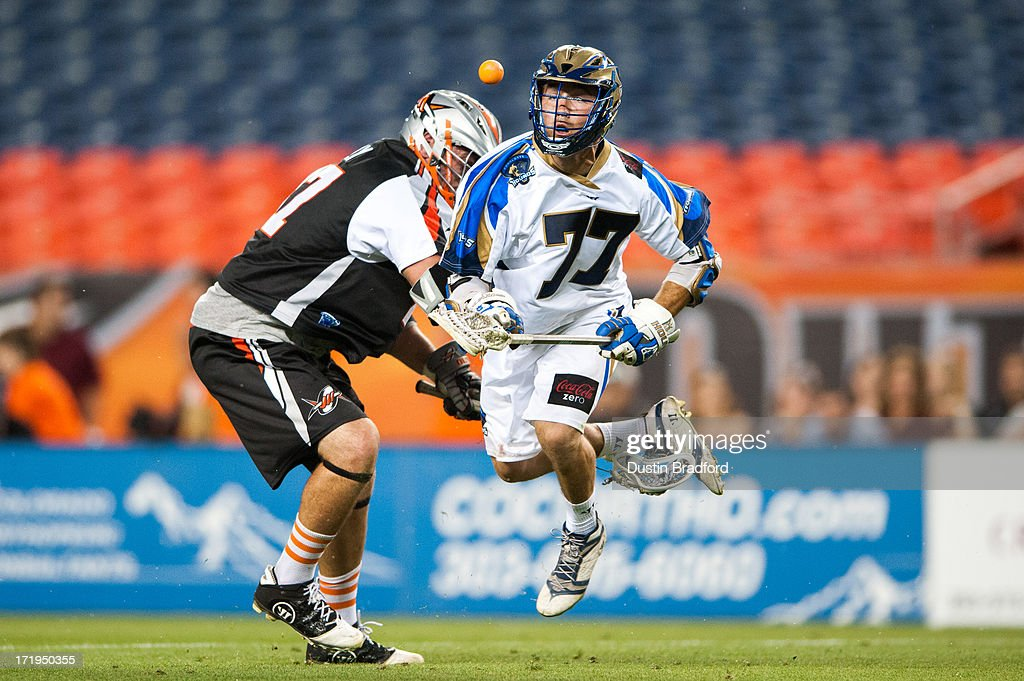Tim Fallon #77 of the Charlotte Hounds is lifted up by Anthony Kelly #47 of the Denver Outlaws during a face-off during a Major League Lacrosse game at Sports Authority Field at Mile High on June 29, 2013 in Denver, Colorado. The Outlaws beat the Hounds 17-11 and improved to 9-0 on the season.