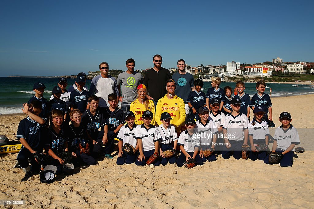 Tim Federowicz, Drew Butera, Chris Withrow and Mike Baxter of the Los Angeles Dodgers pose with players from Illawong and St John Bosco little league during a Los Angeles Dodgers players visit at Bondi Beach on March 19, 2014 in Sydney, Australia.