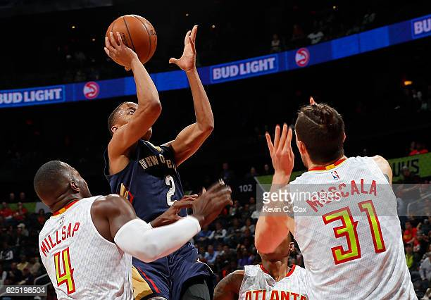 Tim Frazier of the New Orleans Pelicans shoots against Paul Millsap Kent Bazemore and Mike Muscala of the Atlanta Hawks at Philips Arena on November...