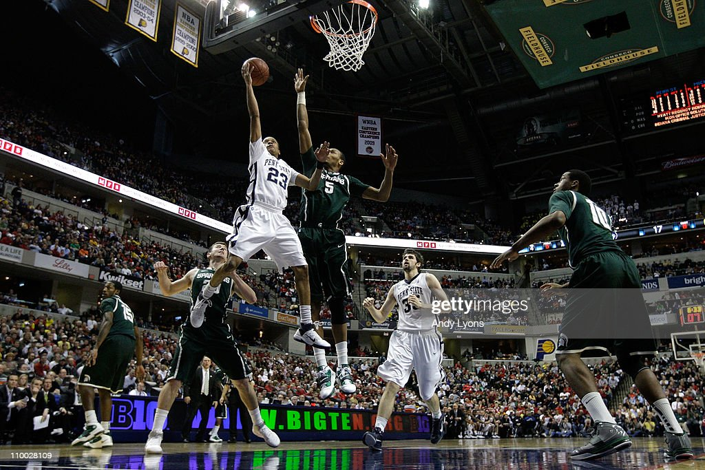 Tim Frazier of the Penn State Nittany Lions drives for a shot attempt against Adreian Payne of the Michigan State Spartans during the semifinals of...