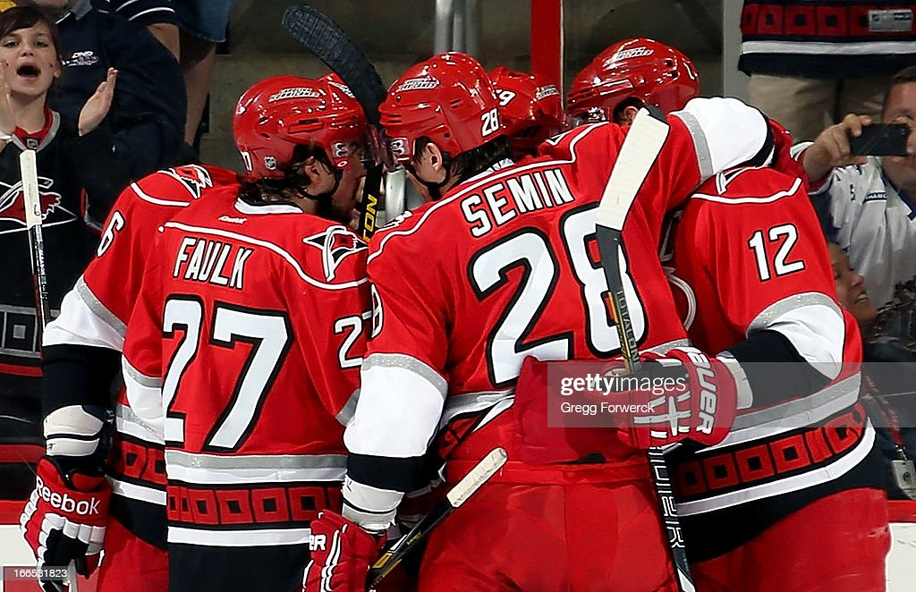 Tim Gleason #6, Justin Faulk #27, Alexander Semin #28 and Eric Staal #12 of the Carolina Hurricanes celebrate a second-period goal scored by Jiri Tlusty #19 against the Boston Bruins during their NHL game at PNC Arena on April 13, 2013 in Raleigh, North Carolina.