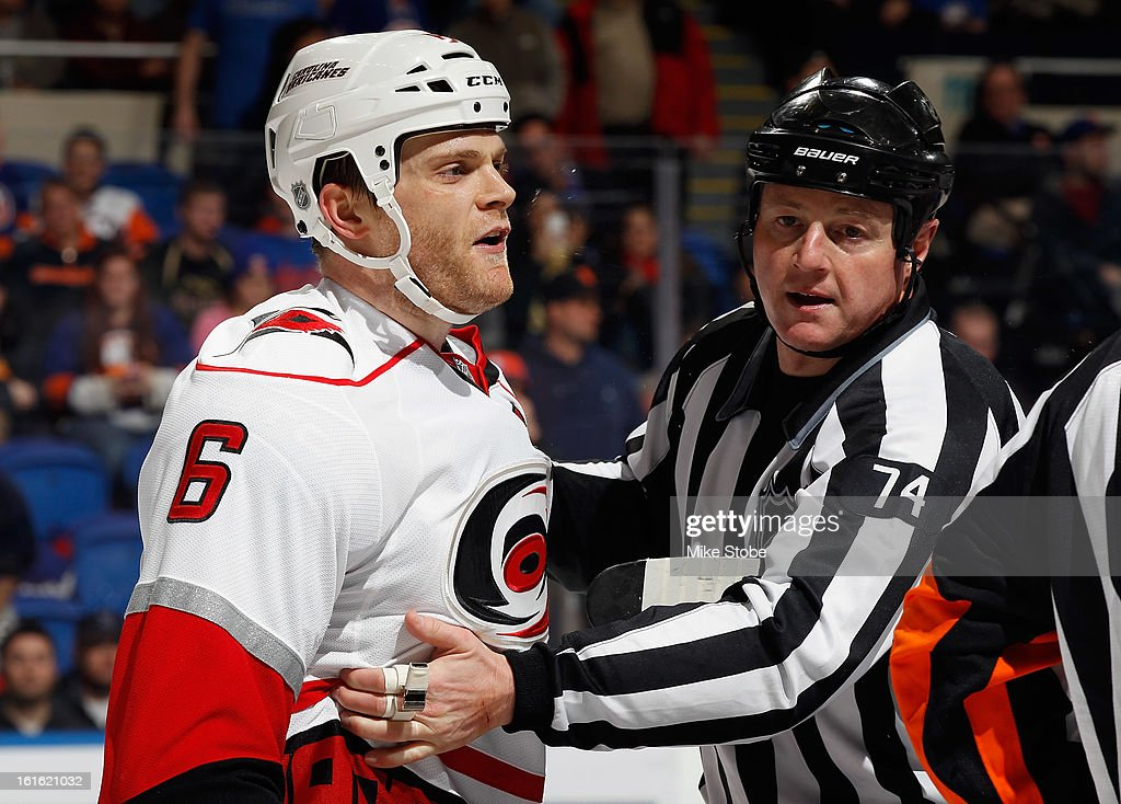 Tim Gleason #6 of the Carolina Hurricanes his held back by linesman Lonnie Cameron #74 during the game against the New York Islanders at Nassau Veterans Memorial Coliseum on February 11, 2013 in Uniondale, New York. The Hurricanes defeated the Islanders 6-4.