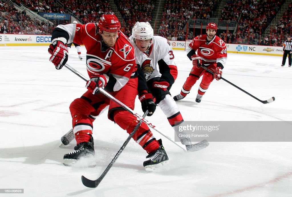 Tim Gleason #6 of the Carolina Hurricanes holds off Jakob Silfverberg #33 of the Ottawa Senators as they battle for the puck during their NHL game at PNC Arena on February 1, 2013 in Raleigh, North Carolina.