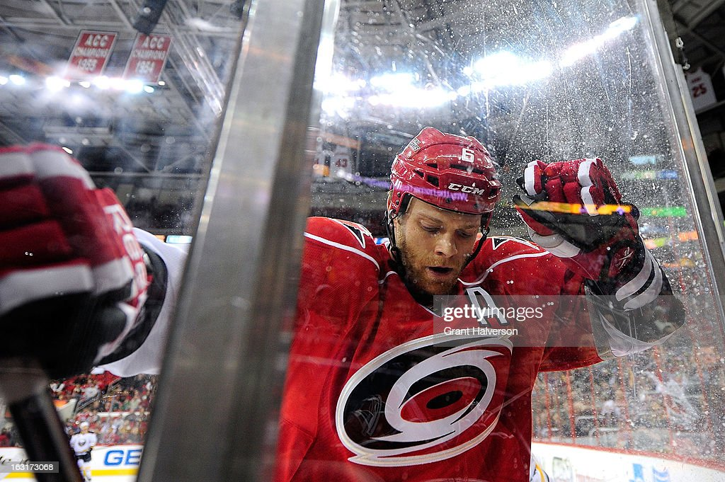 Tim Gleason #6 of the Carolina Hurricanes is checked into the glass by the Buffalo Sabres during play at PNC Arena on March 5, 2013 in Raleigh, North Carolina.