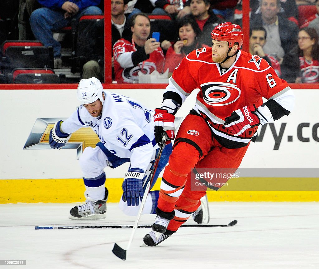 Tim Gleason #6 of the Carolina Hurricanes moves the puck against Ryan Malone #12 of the Tampa Bay Lightning during play at PNC Arena on January 22, 2013 in Raleigh, North Carolina.