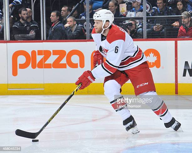 Tim Gleason of the Carolina Hurricanes plays the puck up the ice during first period action against the Winnipeg Jets on October 21 2014 at the MTS...
