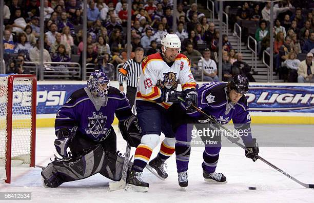 Tim Gleason of the Los Angeles Kings fights for a loose puck with Gary Roberts of the Florida Panthers in front of goalie Mathieu Garon of the Kings...