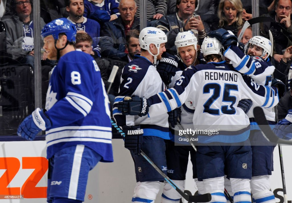 <a gi-track='captionPersonalityLinkClicked' href=/galleries/search?phrase=Tim+Gleason&family=editorial&specificpeople=211575 ng-click='$event.stopPropagation()'>Tim Gleason</a> #8 of the Toronto Maple Leafs skates away as <a gi-track='captionPersonalityLinkClicked' href=/galleries/search?phrase=Olli+Jokinen&family=editorial&specificpeople=202946 ng-click='$event.stopPropagation()'>Olli Jokinen</a> #12 of the Winnipeg Jets celebrates a third period goal with teammates during NHL game action April 5, 2014 at the Air Canada Centre in Toronto, Ontario, Canada.