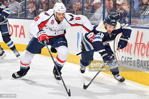 Tim Gleason of the Washington Capitals and Corey Tropp of the Columbus Blue Jackets skate after a loose puck during the third period on March 3 2015...