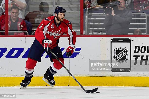 Tim Gleason of the Washington Capitals controls the puck against the Carolina Hurricanes in the first period during an NHL game at Verizon Center on...