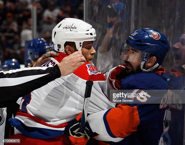 Tim Gleason of the Washington Capitals holds Cal Clutterbuck of the New York Islanders against the boards during the second period in Game Four of...