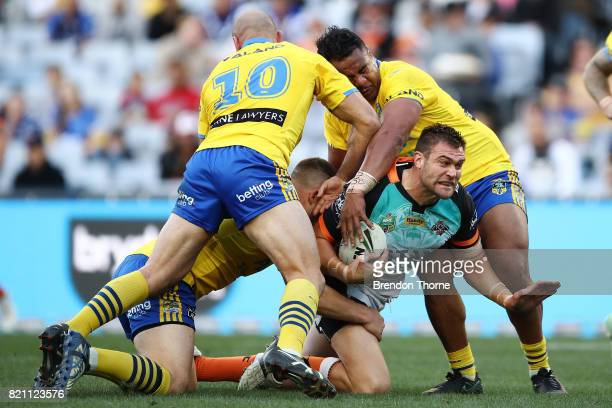 Tim Grant of the Tigers is tackled by the Eels defence during the round 20 NRL match between the Wests Tigers and the Parramatta Eels at ANZ Stadium...