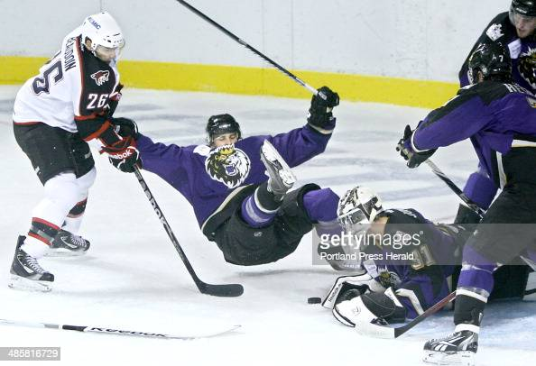 Mathieu Beaudoin of the Portland Pirates left upends Cam Paddock of the Manchester Monarchs and Monarchs' goalie Martin Jones knocks the puck away in...