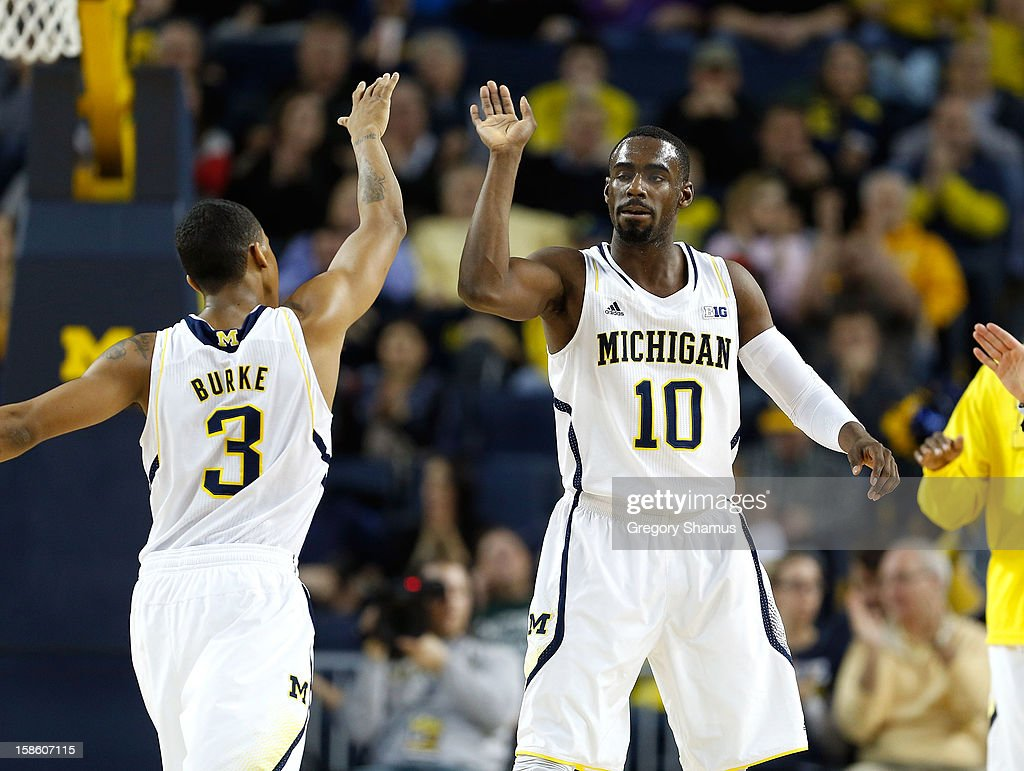 Tim Hardaway Jr. #10 high fives Trey Burke #3 of the Michigan Wolverines after a first half play while playing the Eastern Michigan Eagles at Crisler Center on December 20, 2012 in Ann Arbor, Michigan.