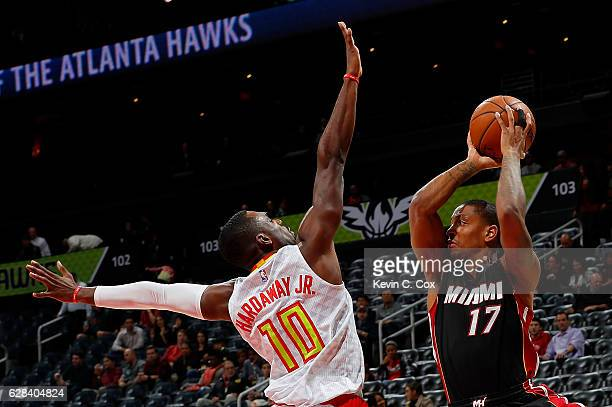 Tim Hardaway Jr #10 of the Atlanta Hawks defends against Rodney McGruder of the Miami Heat at Philips Arena on December 7 2016 in Atlanta Georgia...