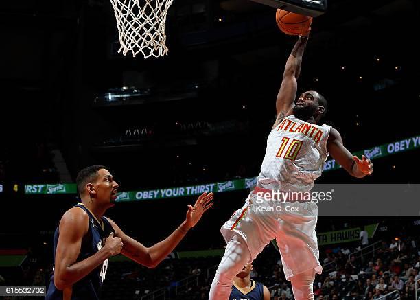 Tim Hardaway Jr #10 of the Atlanta Hawks dunks against Alexis Ajinca of the New Orleans Pelicans at Philips Arena on October 18 2016 in Atlanta...