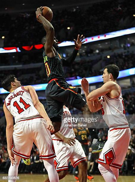 Tim Hardaway Jr #10 of the Atlanta Hawks goes up for a dunk between Doug McDermott and Paul Zipser of the Chicago Bulls at the United Center on...