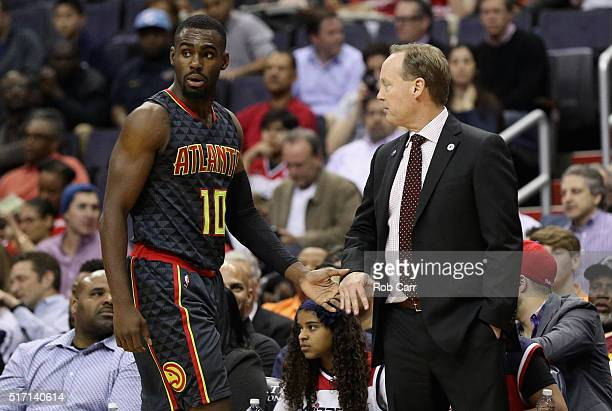 Tim Hardaway Jr #10 of the Atlanta Hawks high fives head coach Mike Budenholzer in the first half against the Washington Wizards at Verizon Center on...