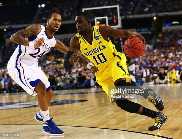 Tim Hardaway Jr #10 of the Michigan Wolverines drives against Travis Releford of the Kansas Jayhawks during the South Regional Semifinal round of the...