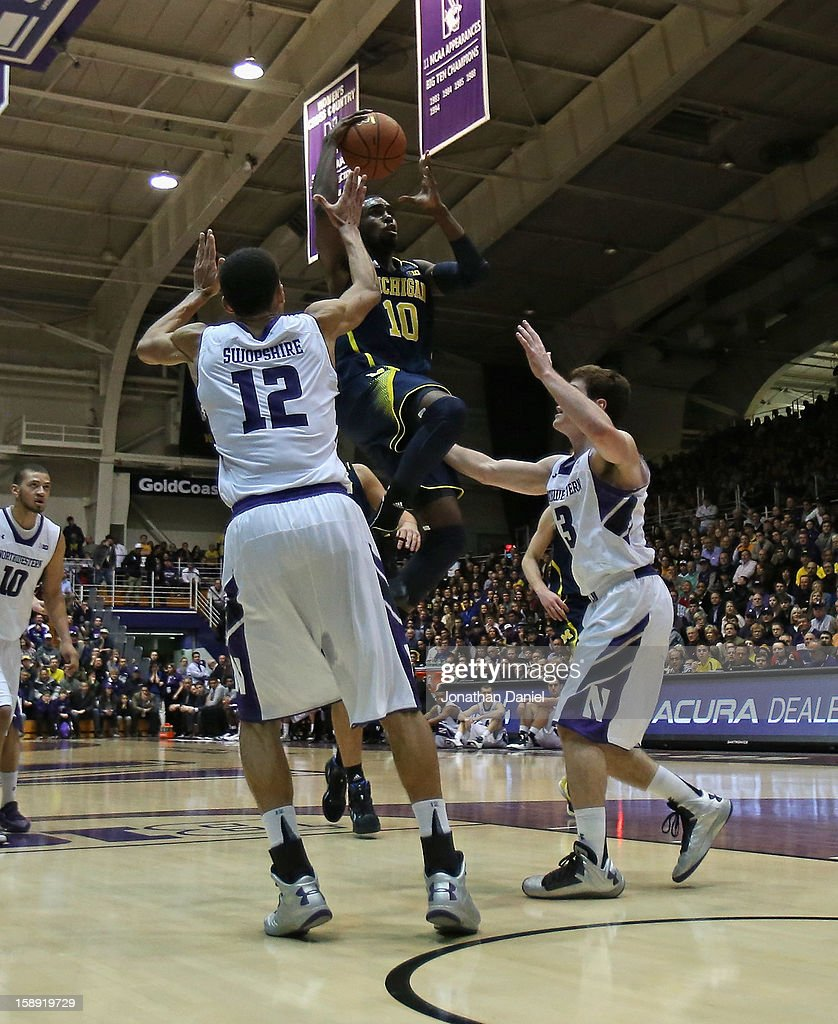 Tim Hardaway Jr. #10 of the Michigan Wolverines drives between Jared Swopshire #12 and Dave Sobolewski #3 of the Northwestern Wildcats at Welsh-Ryan Arena on January 3, 2013 in Evanston, Illinois. Michigan defeated Northwestern 94-66.