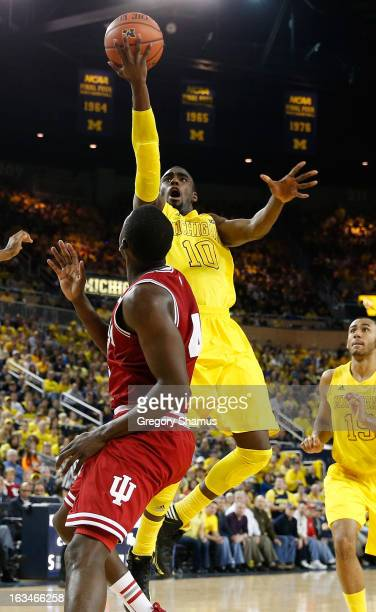 Tim Hardaway Jr #10 of the Michigan Wolverines gets to the basket over Victor Oladipo of the Indiana Hoosiers during the first half at Crisler Center...