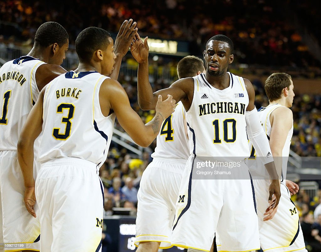 Tim Hardaway Jr. #10 of the Michigan Wolverines high fives Trey Burke #3 and Glenn Robinson III #1 of the Michigan Wolverines during the first half while playing the Nebraska Cornhuskers at Crisler Center on January 9, 2013 in Ann Arbor, Michigan. Michigan won the game 62-47.