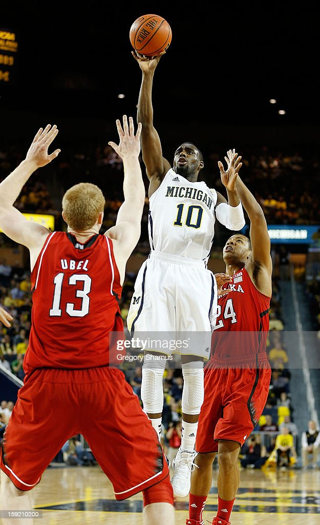 Tim Hardaway Jr. #10 of the Michigan Wolverines takes a first half shot between Brandon Ubel #13 and Dylan Talley #24 of the Nebraska Cornhuskers at Crisler Center on January 9, 2013 in Ann Arbor, Michigan.