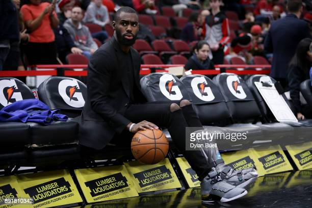 Tim Hardaway Jr #3 of the New York Knicks dribbles a ball while sitting on the bench before the game against the Chicago Bulls at the United Center...