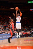 Tim Hardaway Jr #5 of the New York Knicks shoots against Terrence Ross of the Toronto Raptors during the game on April 16 2014 at Madison Square...