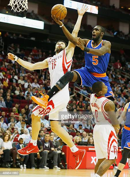 Tim Hardaway Jr #5 of the New York Knicks takes a shot over Kostas Papanikolaou and Isaiah Canaan of the Houston Rockets at the Toyota Center on...
