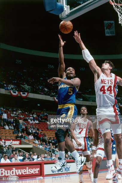 Tim Hardaway of the Golden State Warriors shoots a hook shot against the New Jersey Nets during an NBA game at the Brendan Byrne Arena in 1989 in...