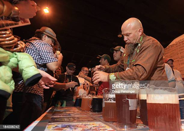 Tim Hawn brewmaster for Dogfish Head Craft Brewery of Milton Delaware pours beers for festival goers at the 32nd annual Great American Beer Festival...