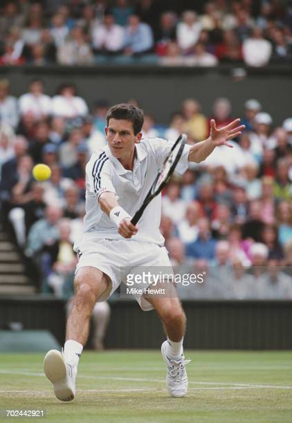 Tim Henman of Great Britain makes a backhand return against Andre Sa during their Quarter Final match of the Wimbledon Lawn Tennis Championship on 5...