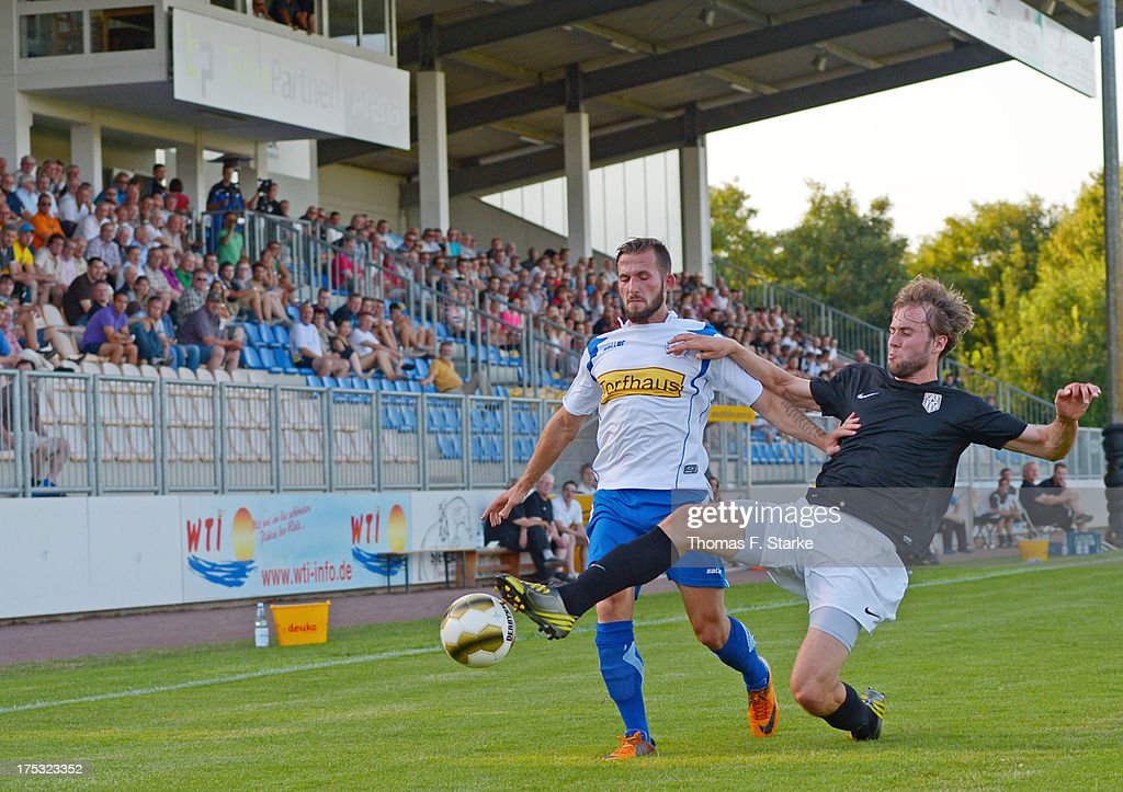 Tim Hofmann (R) of Cloppenburg tackles Tezcan Karabulut of Goslar during the Regionalliga North match between BV Cloppenburg and Goslarer SC at stadium Cloppenburg on August 2, 2013 in Cloppenburg, Germany.
