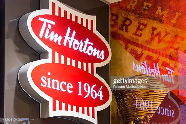 Tim Hortons coffeshop signage reflected on glass the sign having eight red vertical lines with the phrases 'Tim Hortons' and 'since 1964' written in...