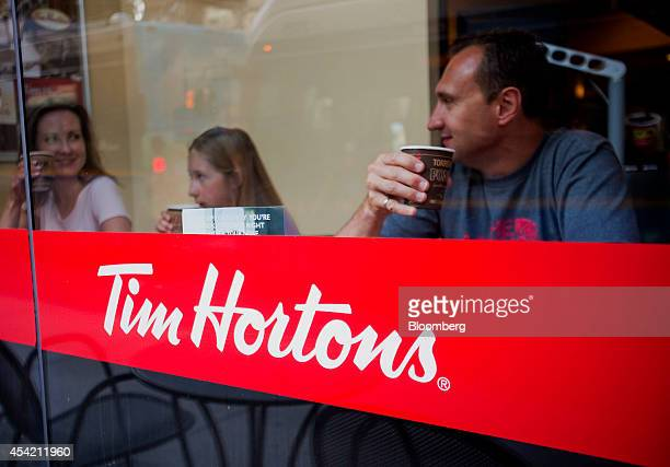 Tim Hortons Inc signage is displayed as customers drink coffee inside a restaurant in downtown Vancouver British Columbia Canada on Tuesday Aug 26...