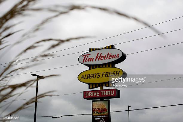 Tim Hortons Inc signage stands outside of a restaurant in Oakville Ontario Canada on Monday Sept 16 2013 Tim Hortons Inc Chief Executive Officer Marc...
